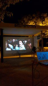 El alcalde de Monreal del Llano reivindica el paso del autobús por su pueblo utilizando la marquesina para proyectar cine de verano